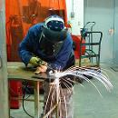Student Chandra Shin welds in the welding room