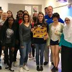 Madeline Carpenter Rizzo (holding the I survived...sign) with Chattahoochee High Principal, Tim Corrigan, and students at the end of the first week!