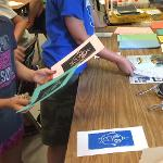Elementary student of Amy Norton reviews his prints of different colors.