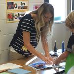 Art education student Amy Norton demonstrates printmaking techniques to her elementary students.