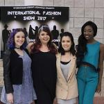Student models pose in front of the International Fashion Week poster on Kennesaw Campus