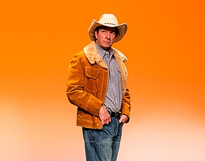 Image on a cowboy on blank stage with orange light