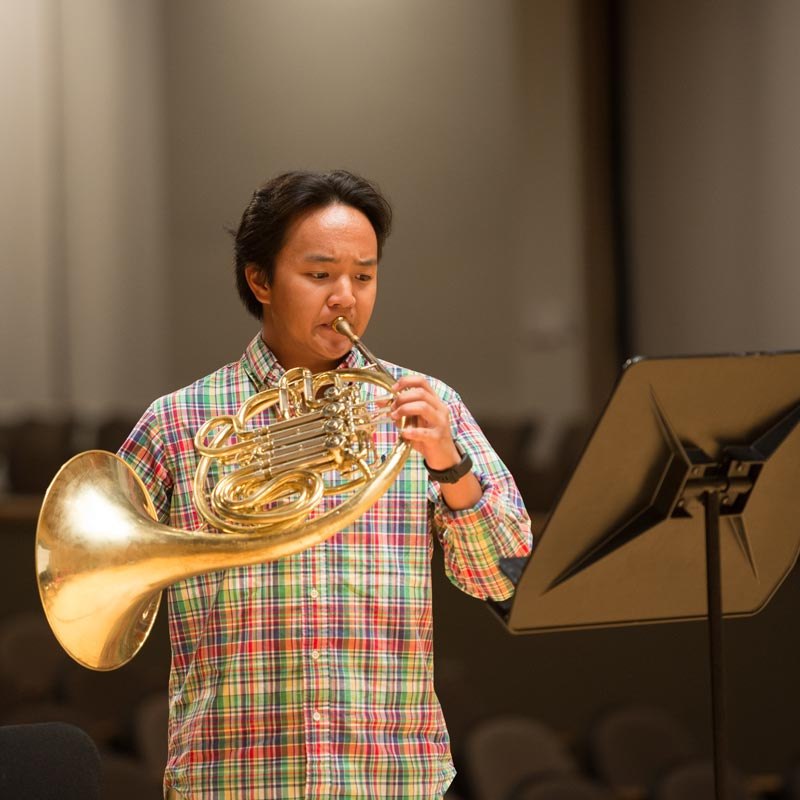 A student reading off music and playing his horn.