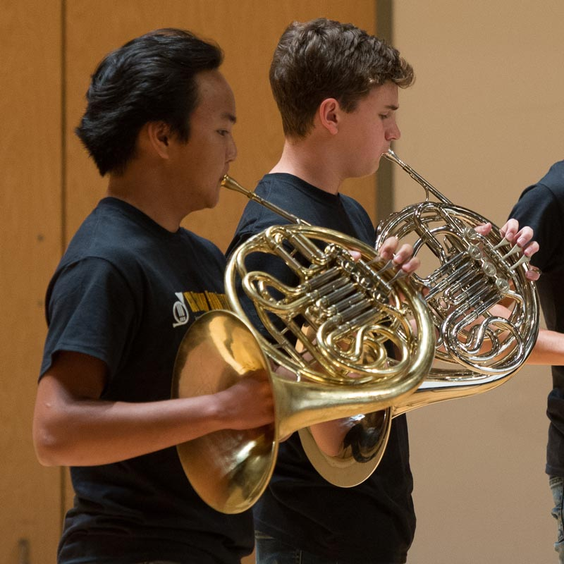 Two students playing the horn.