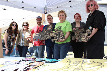 students show their relief printing plates at an event at the Zuckerman Museum of Art