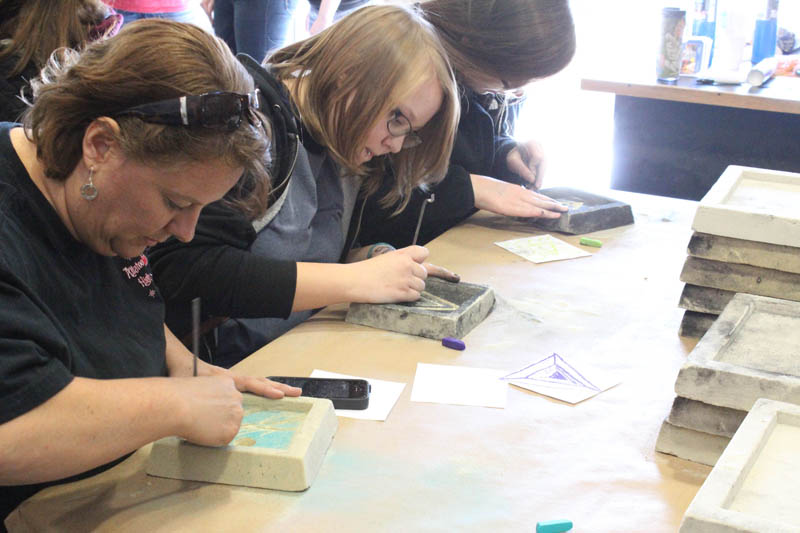 Attendees of the Spring Arts Festival make designs in their scratch molds