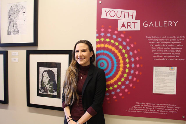 "Alyssa McCune poses with her students' artworks at Kennesaw Hall through the ZMA/Bagwell/SOAAD collaborative ""Youth Art Gallery"" project."