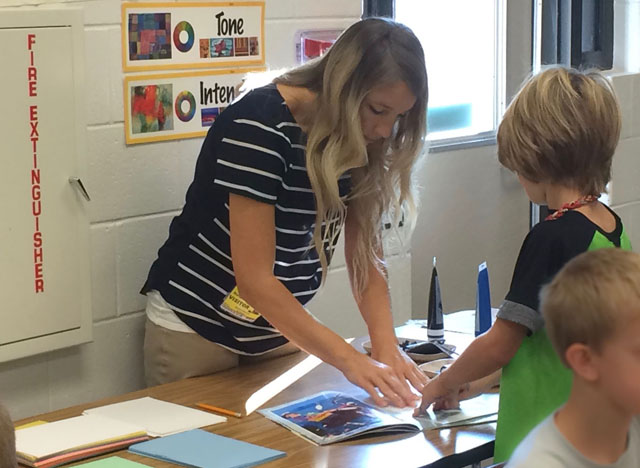 Alumna teacher Amy Norton demonstrates printing for her elementary students.