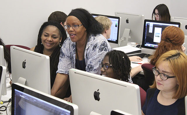 Professor helping students with design on Mac computers
