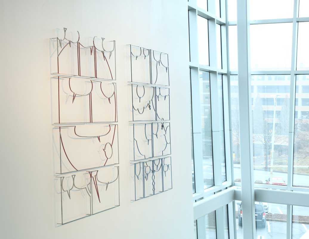 "Image of Greely Myatt's installation at the ZMA featuring ""Untitled Pages (Hagar) and (Beetle Bailey) created in 2011 with Painted and polished steel and air, measuring 73 x 53 x 3"" each. The two ""pages"" created by the artist are installed side by side on the wall. (Hagar) on the left features multiple steel frames of different sizes in 4 rows. All eight frames feature different sized thought bubbles. The thought bubbles come together to create an abstracted smiley face on the work on the left. (Beetle Bailey) on the right features ten different sized frames arranged into four rows. The motif in this untitled page consists of several small thought bubbles throughout and three larger thought bubbles that interact in multiple frames."